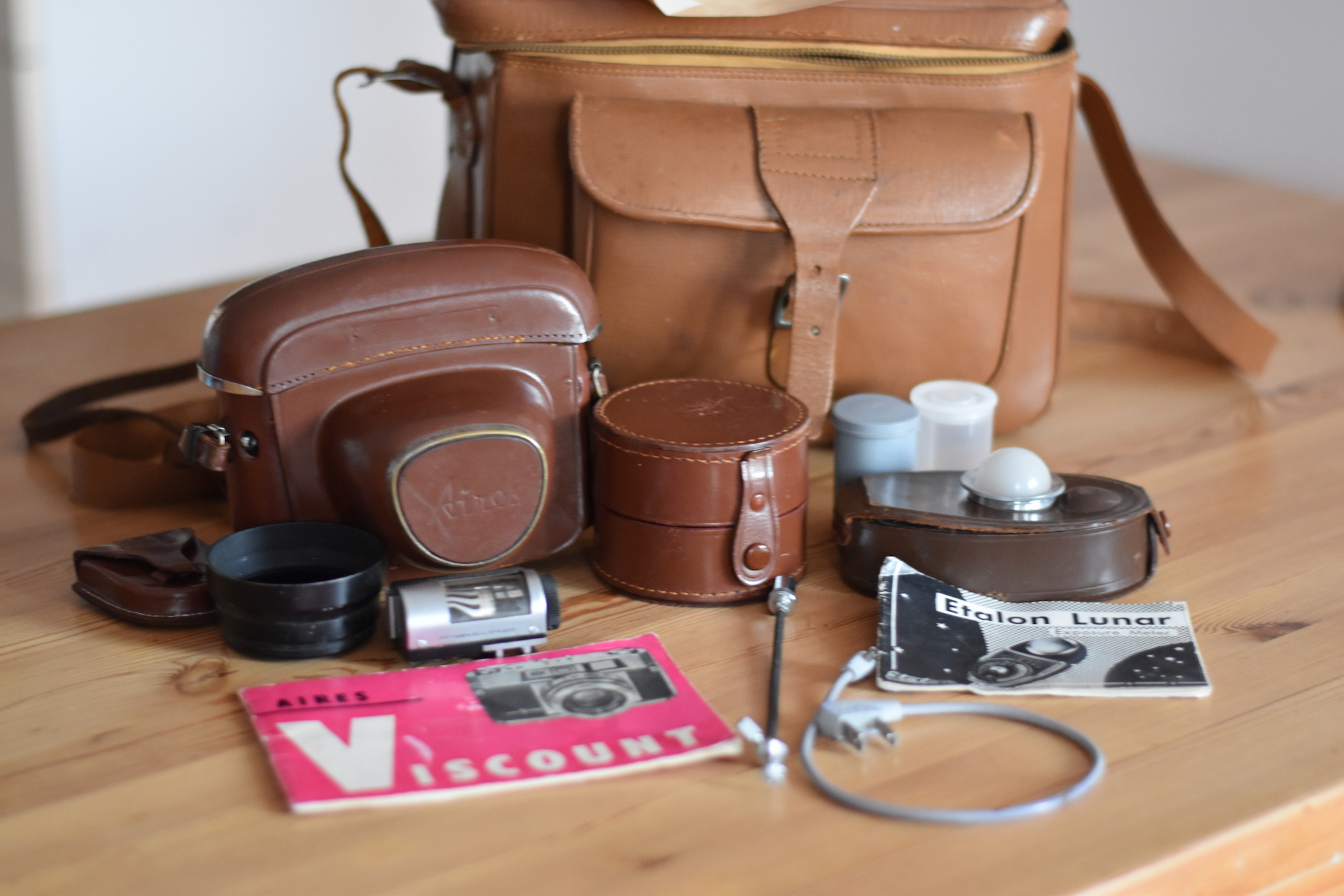 A group of camera equipment in front of a leather camera bag. Including a camera in a full leather case, a leather lens box, a light meter, some film canisters, and a manual