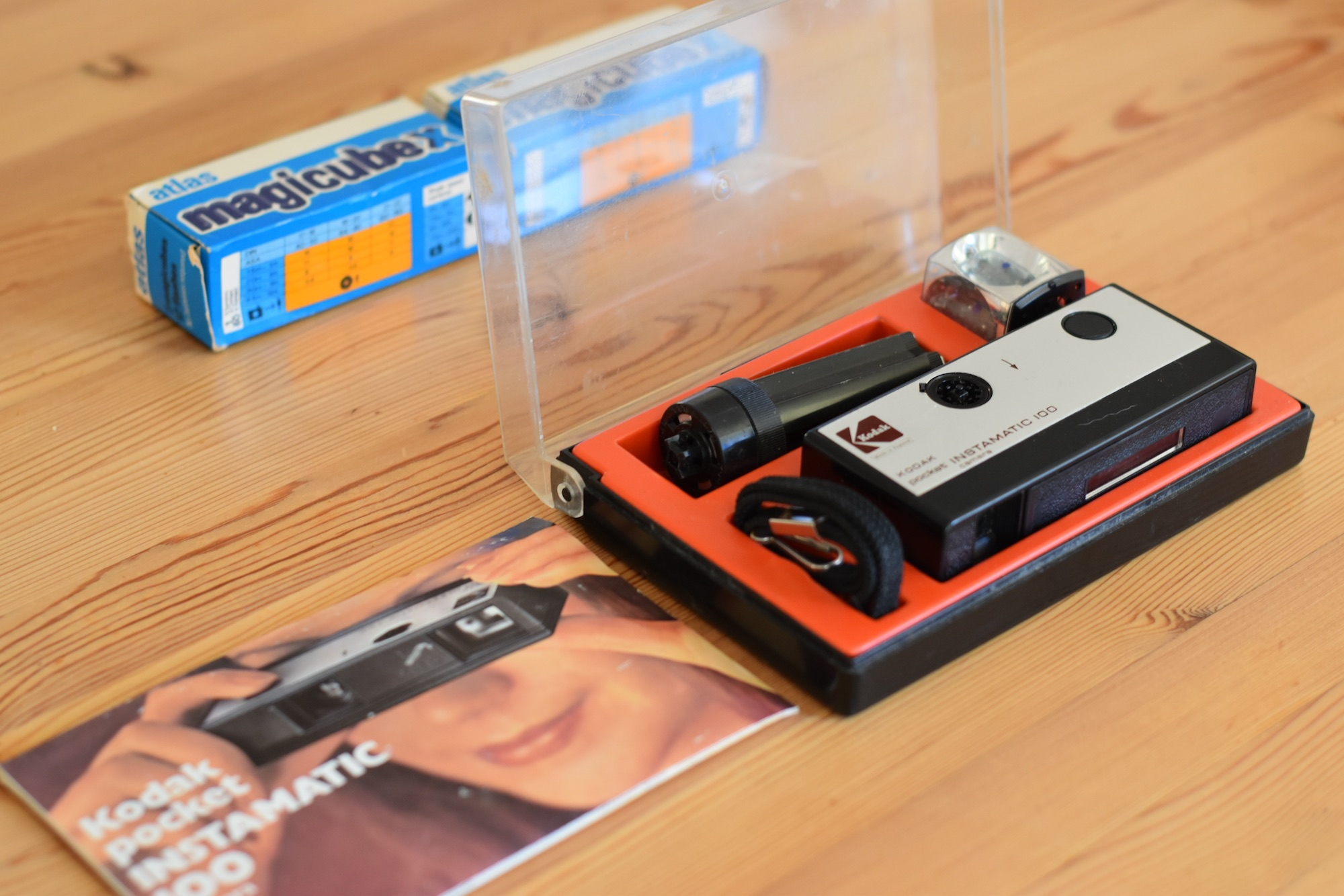 Kodak Instamatic Pocket 100 in original plastic box. Box top is clear, box base is black with a red plastic insert that holds the camera components. Manual is on table in front of box, has a picture of a young woman holding the camera up to her eye
