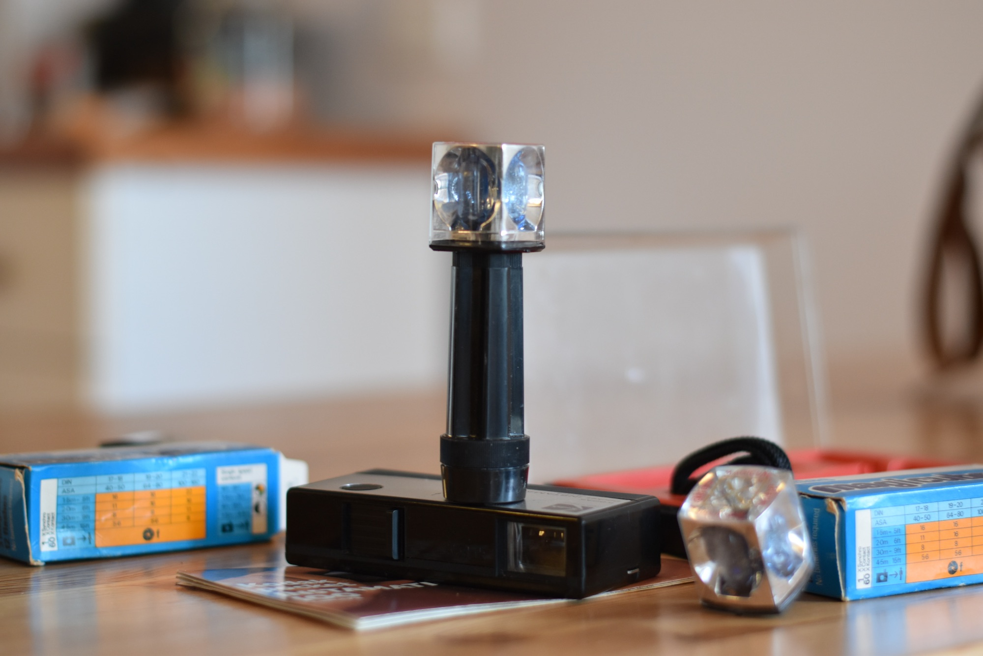 Magicube flash unit with four single-use flash bulbs. Attached to camera directly or with provided extension pole. Magicube is small and silver with a clear plastic cover, two boxes of Magicubes are shown in the background