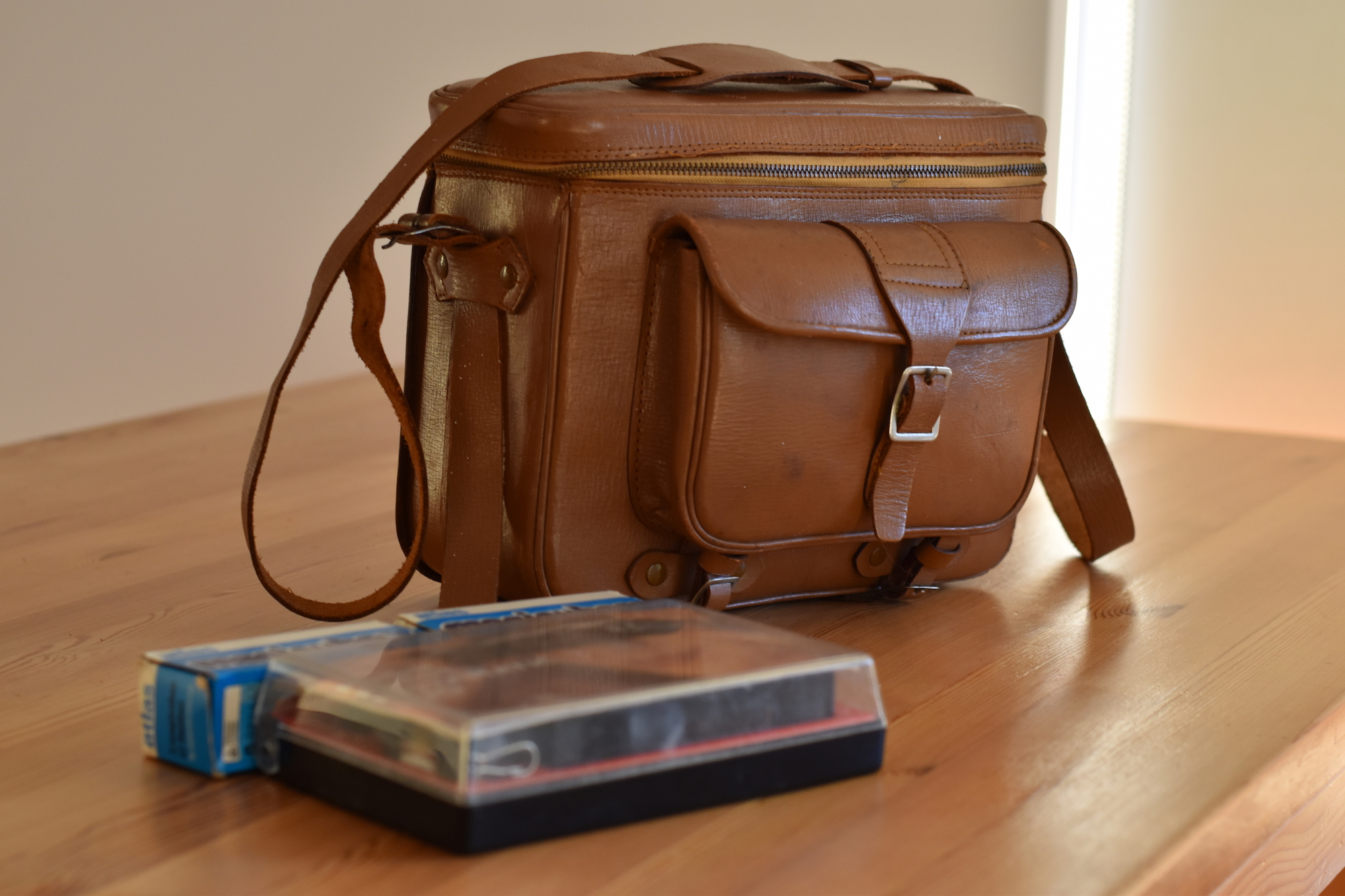 Kodak Instamatic Pocket 100 in original plastic box in front of a light brown leather camera bag with zip-around top and front buckled pocket