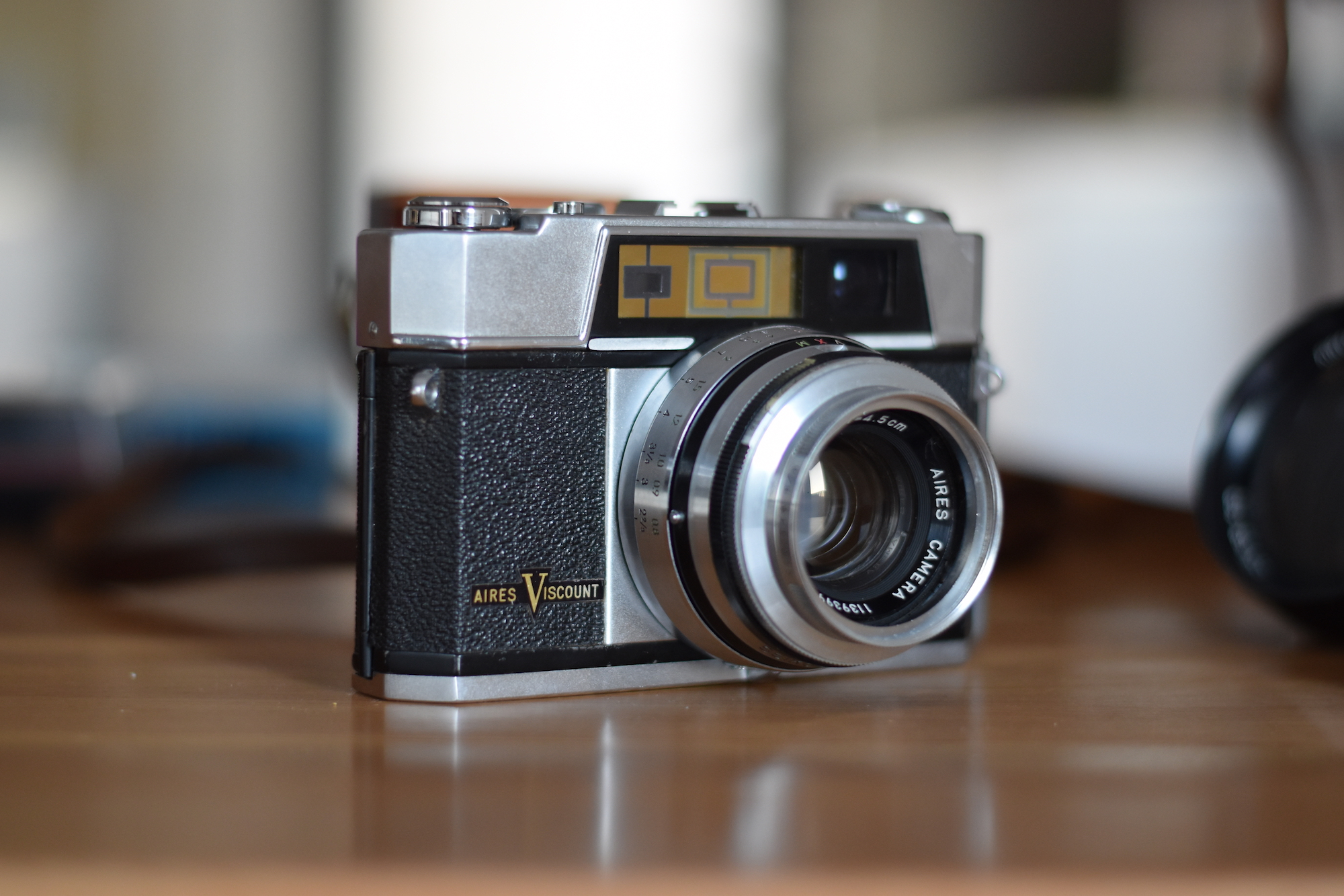 An Aires Viscount rangefinder camera. The base is silvery, the body black leatheret and the top is silvery.
